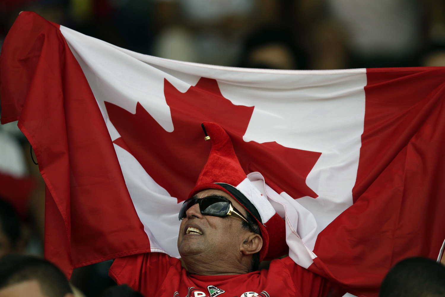 A supporter holds up a Canadian flag before a World Cup 2014 qualifying soccer game between Canada and Cuba in Havana, June 8, 2012. THE ASSOCIATED PRESS/Franklin Reyes