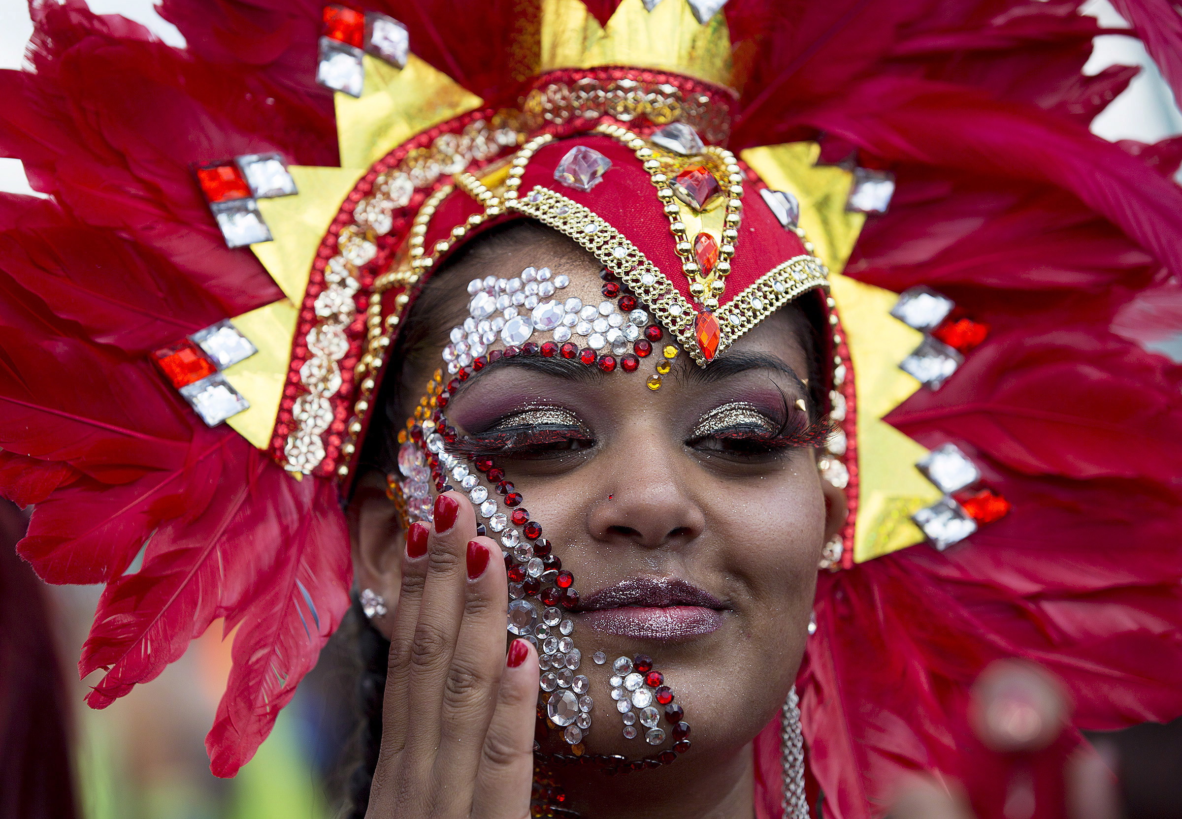 A parader checks on her jewels during the Caribbean Carnival in Toronto on Aug. 3, 2013. THE CANADIAN PRESS/Michelle Siu