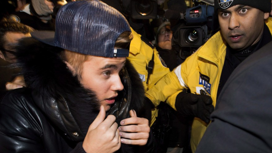 Justin Bieber is swarmed by media and police officers as he surrenders to Toronto police on Jan. 29, 2014. THE CANADIAN PRESS/Nathan Denette