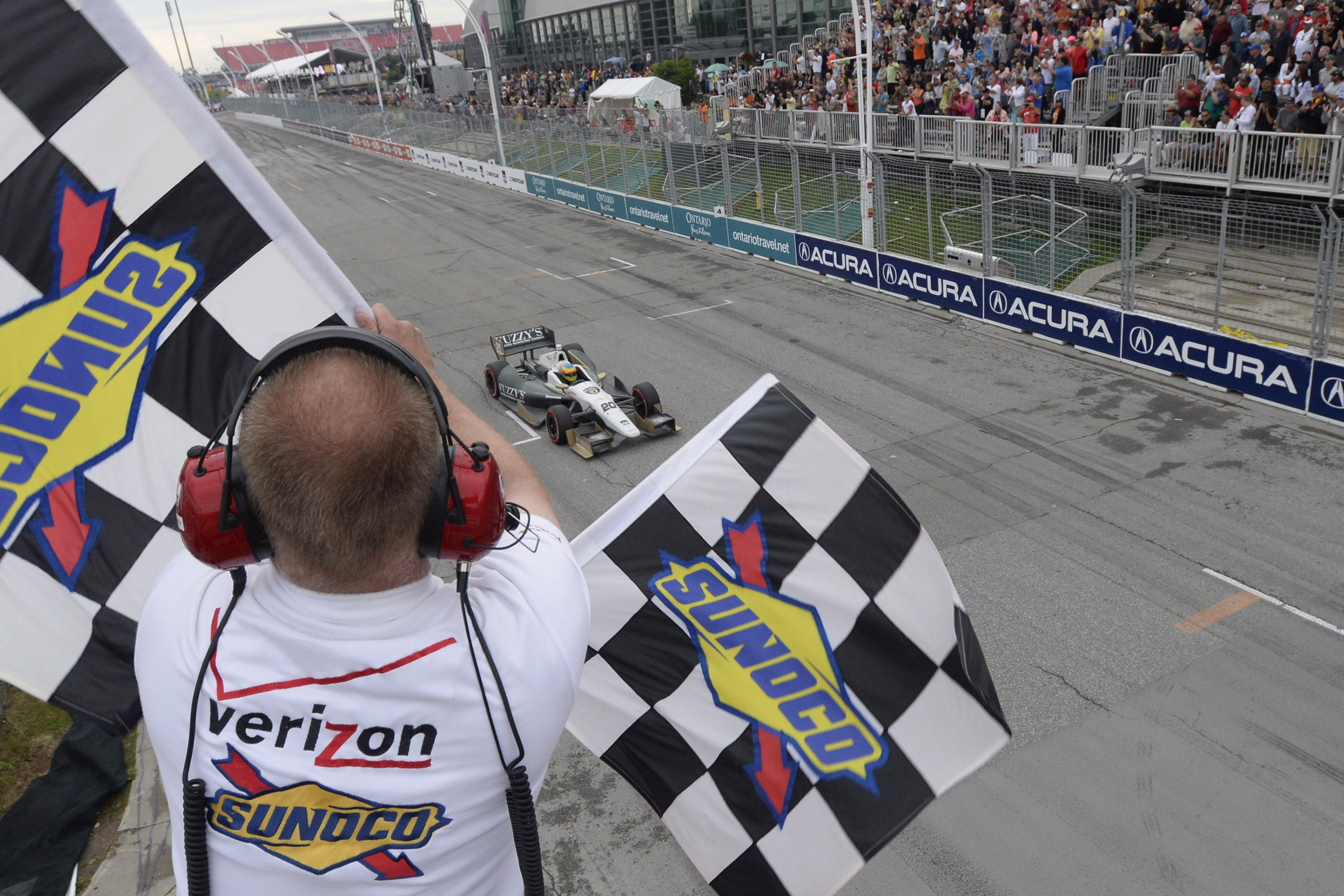 Mike Conway takes the checkered flag to win the second race of the day at the Toronto Indy race on July 20, 2014. THE CANADIAN PRESS/Frank Gunn