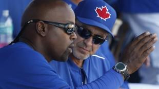 Toronto Blue Jays guest instructor Carlos Delgado, left, gestures as he talks with the Blue Jays hitting coach Brook Jacoby while watching a spring training baseball game against the Tampa Bay Rays in Dunedin, Fla., Wednesday, March 18, 2015. (AP Photo/Kathy Willens)
