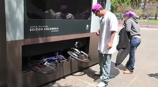 A man receives a bike from a vending machine. Photo via inhabitat.com.