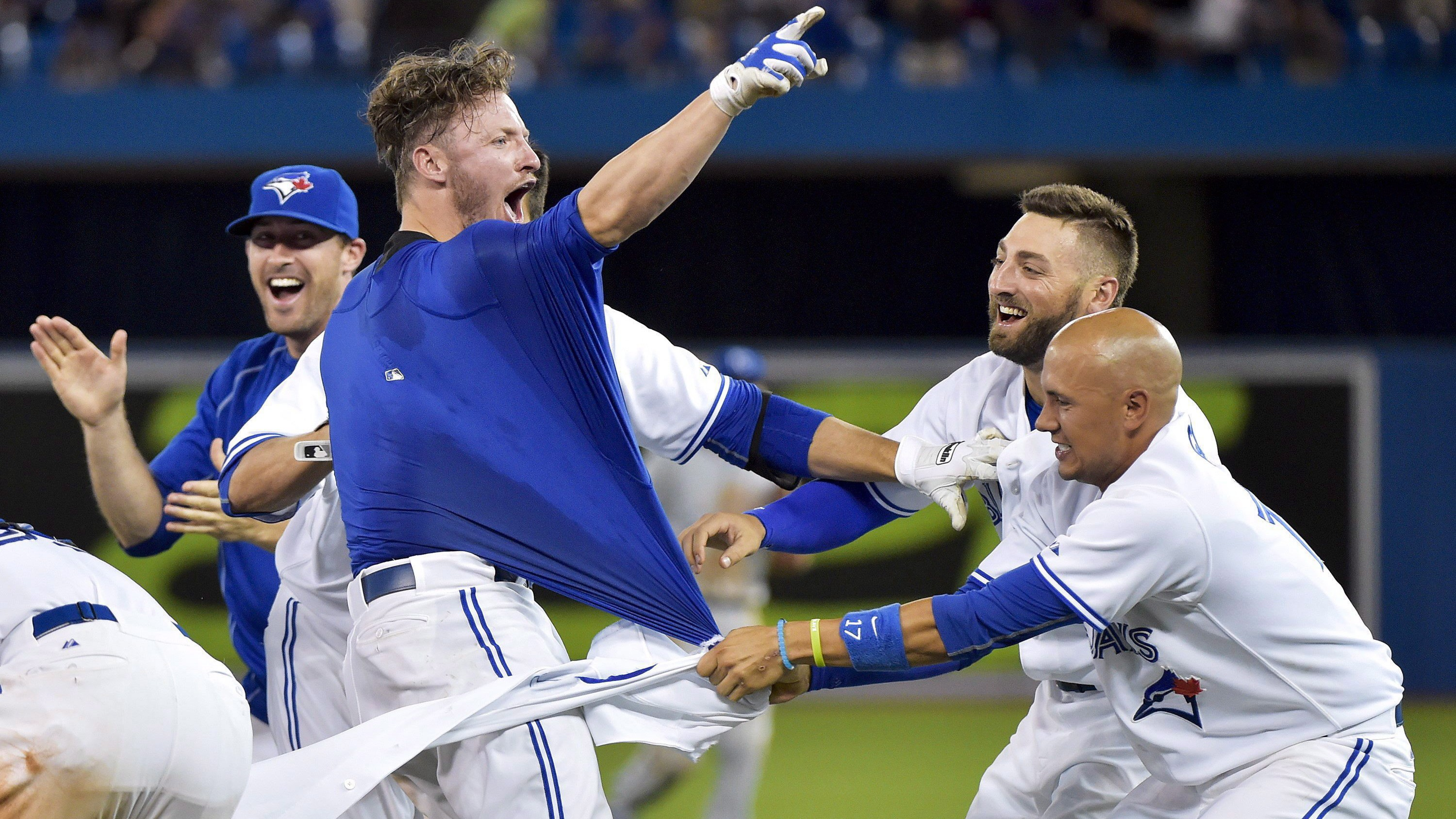 Toronto Blue Jays third baseman Josh Donaldson, second right reacts with teammates, after hitting a RBI single to defeat the Kansas City Royals during 11th inning AL baseball action in Toronto on July 31, 2015. THE CANADIAN PRESS/Nathan Denette