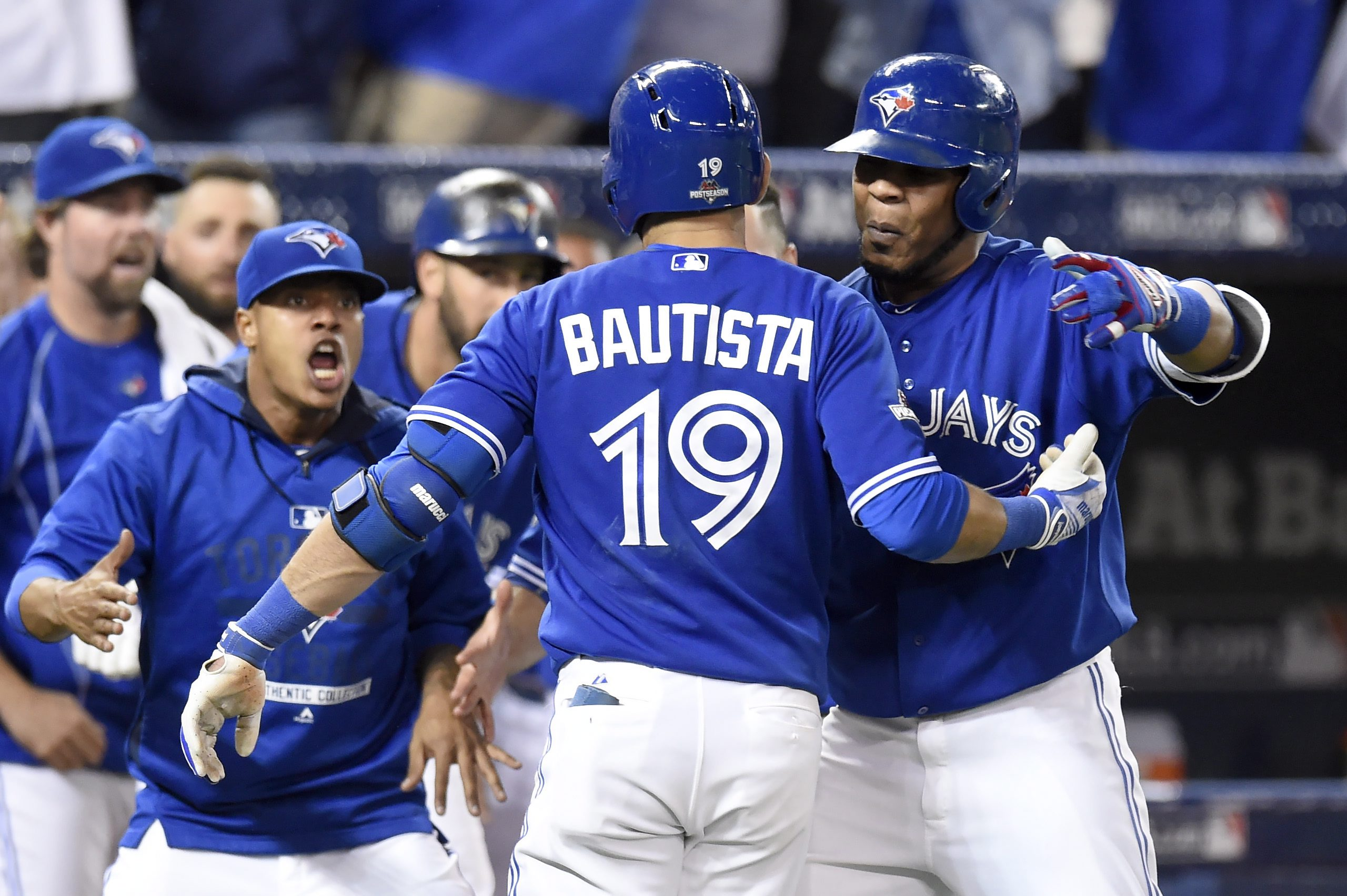 Toronto Blue Jays' Jose Bautista, centre, celebrates with Edwin Encarnacion, right, and Marcus Stroman after hitting a three-run home run against the Texas Rangers during the seventh inning of game 5 American League Division Series baseball action in Toronto on Wednesday, Oct. 14, 2015. THE CANADIAN PRESS/Frank Gunn