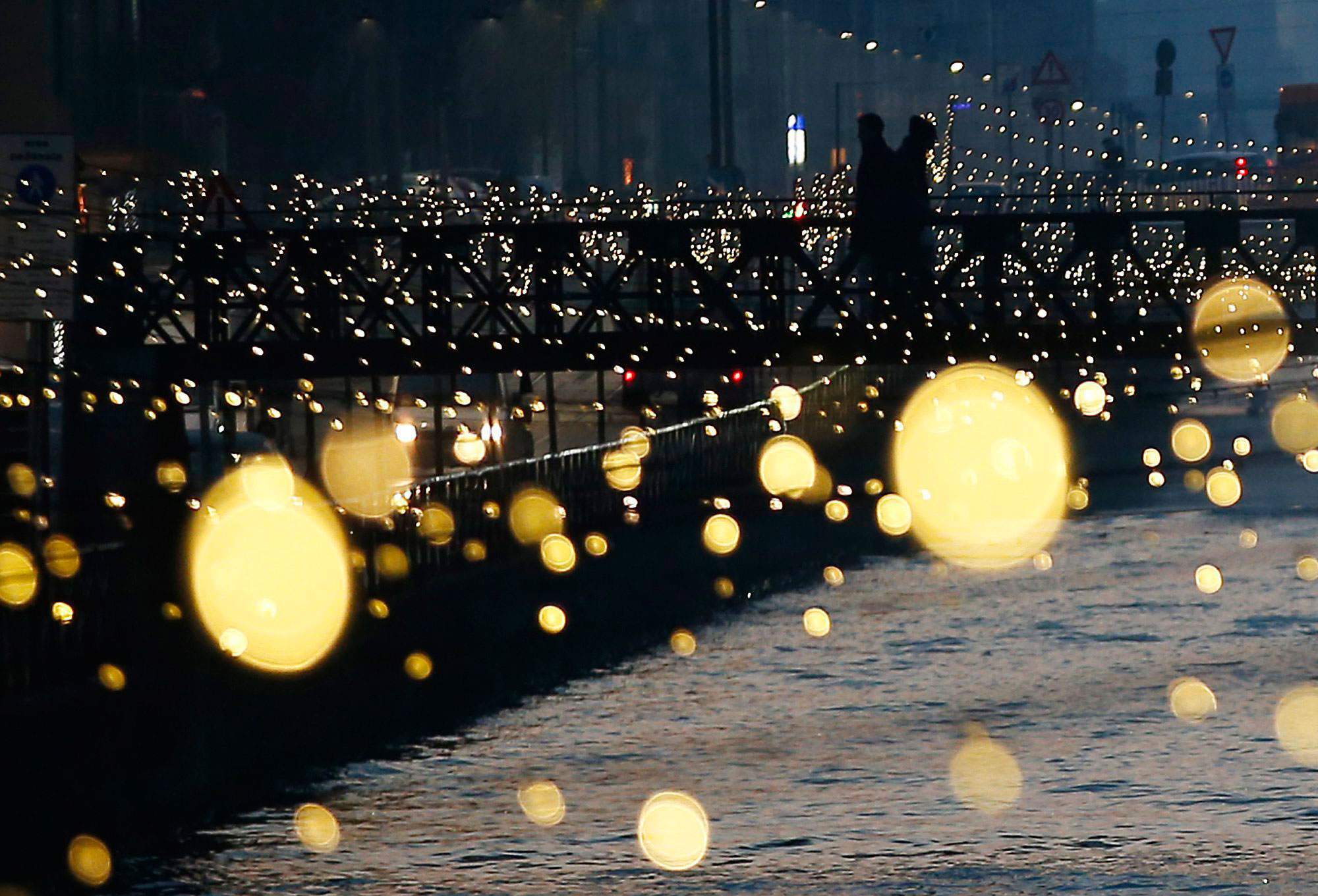 People walk on a bridge as Christmas lights illuminate the Darsena dei Navigli, the neighborhood named for the canals that run through this area of Milan, Italy, on Dec. 16, 2015. THE ASSOCIATED PRESS/Antonio Calanni.