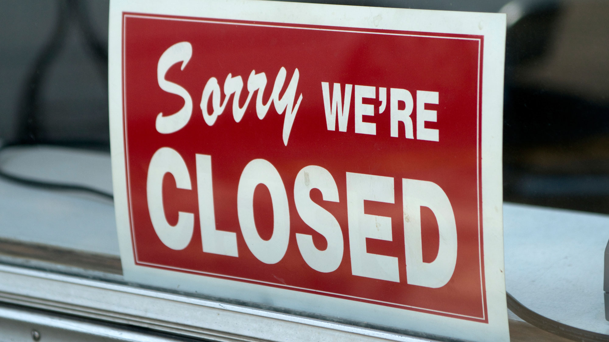 A closed sign on a storefront. GETTY IMAGES/Steve Goodwin