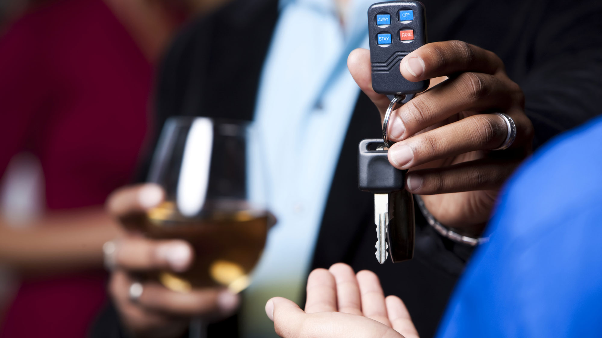 A person drinking hands over his keys to a designated driver. GETTY IMAGES/Jacom Stephens.