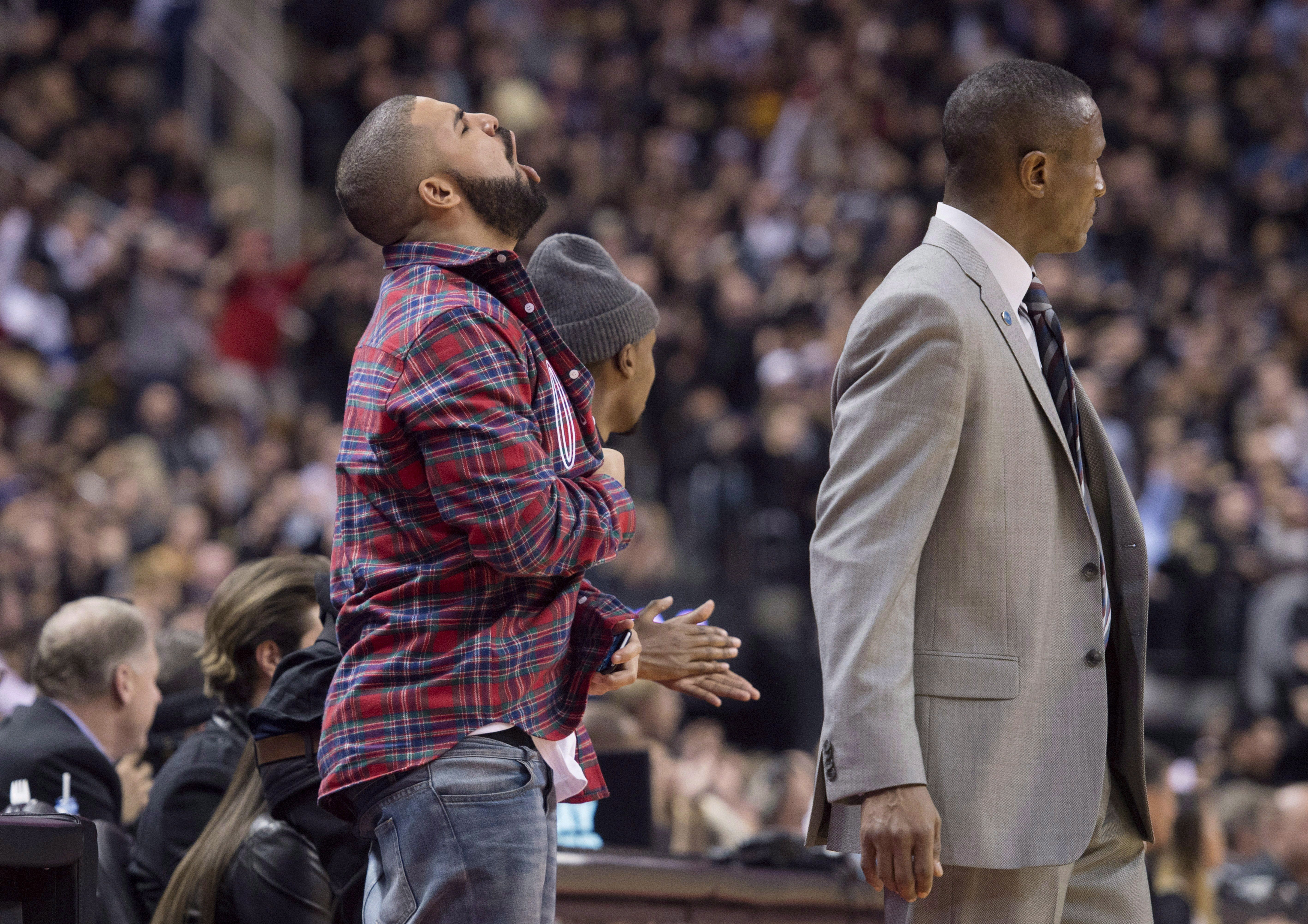 Drake, left, celebrates next to Toronto Raptors head coach Dwane Casey during Drake night at the NBA basketball game between the Raptors and Cleveland Cavaliers in Toronto on Nov. 25, 2015. THE CANADIAN PRESS/Darren Calabrese.