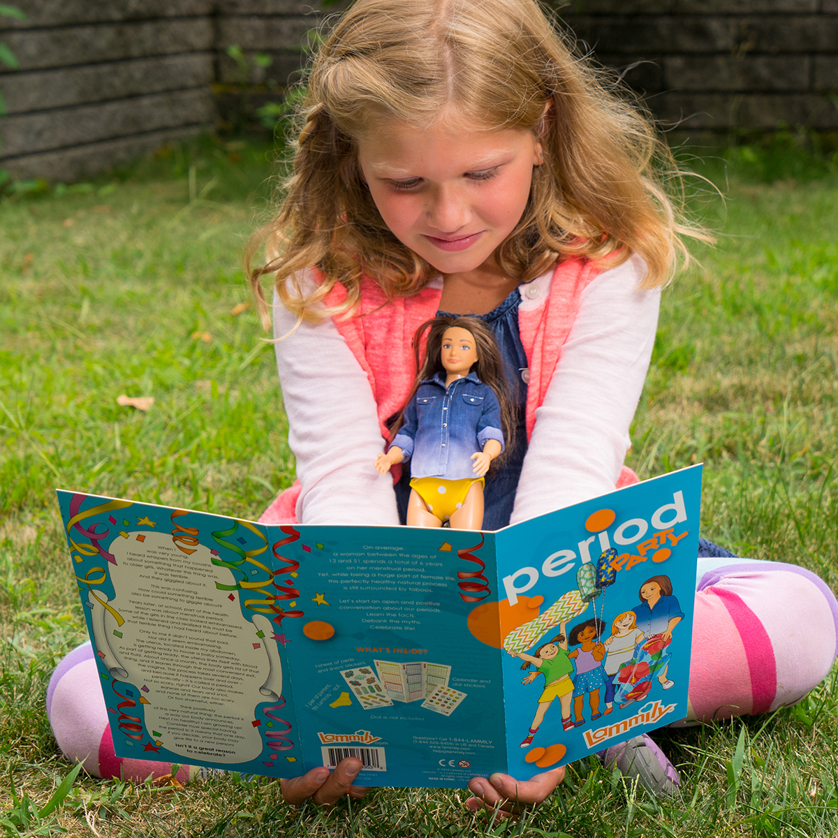 A young girl reads about menstruation while holding a Lammily doll. Image credit: LAMMILY.