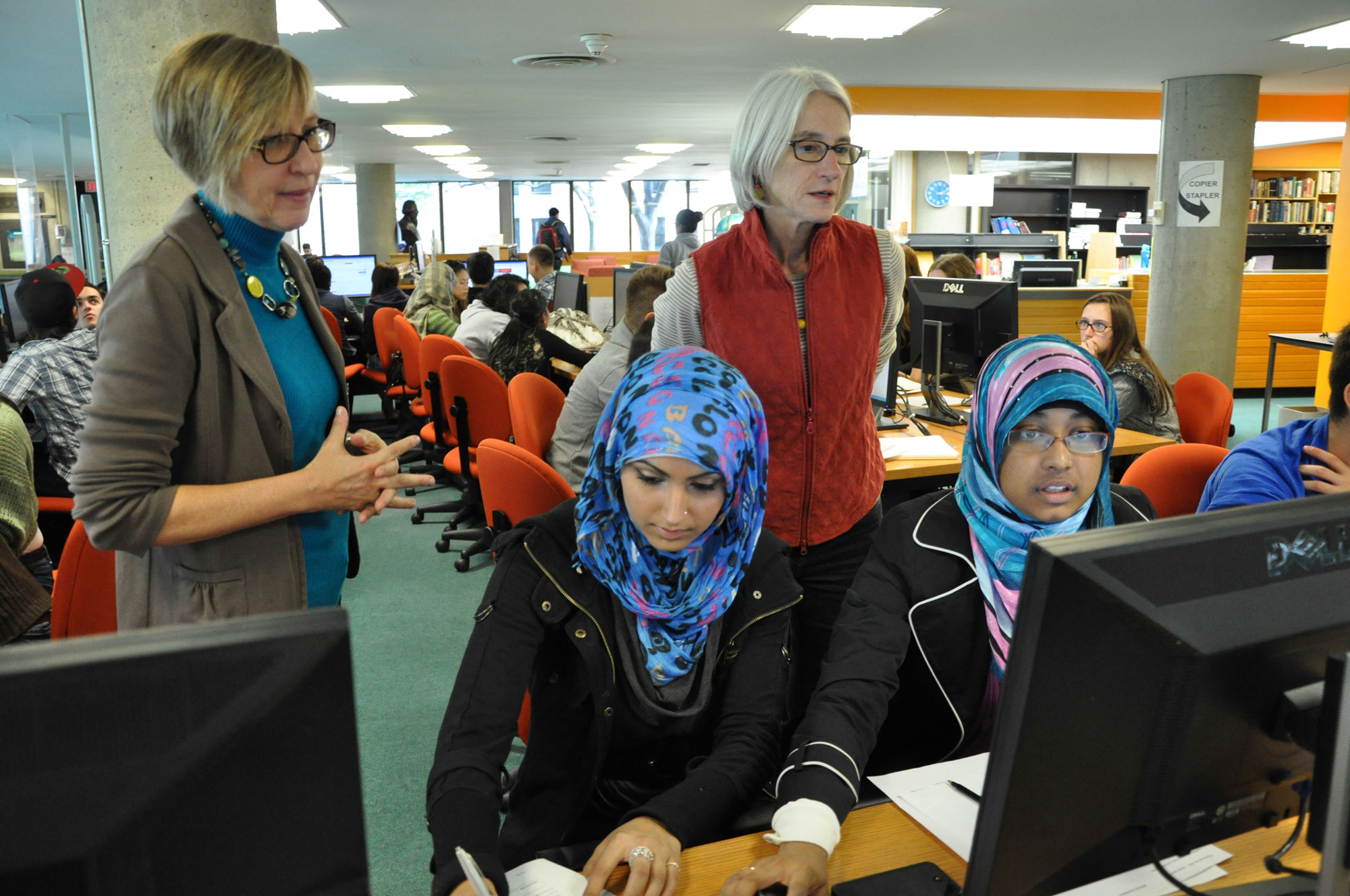Librarians helping students at University of Toronto's New College Library. UNIVERSITY OF TORONTO.