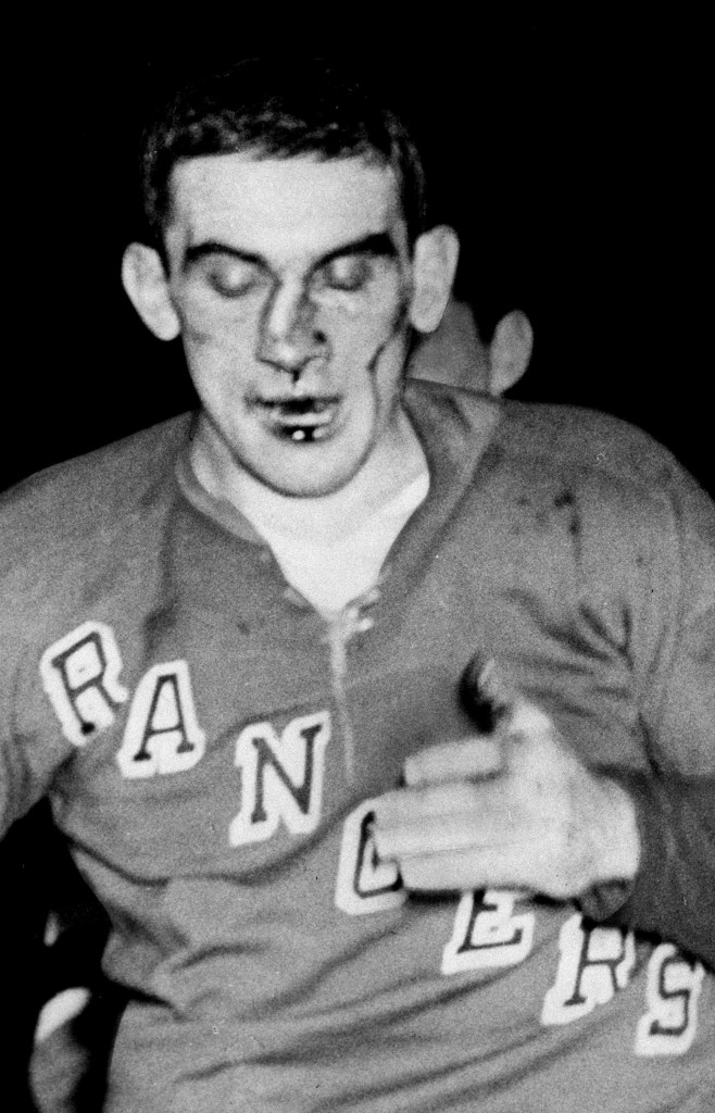 New York Rangers defenseman Lou Fontinato, his nose broken and bent towards his ear, heads to the dressing room after a five minute fight with Detroit Red Wings' Gordie Howe during NHL action at Madison Square Garden on Feb. 2, 1959. The Canadian Press/AP/New York Daily News