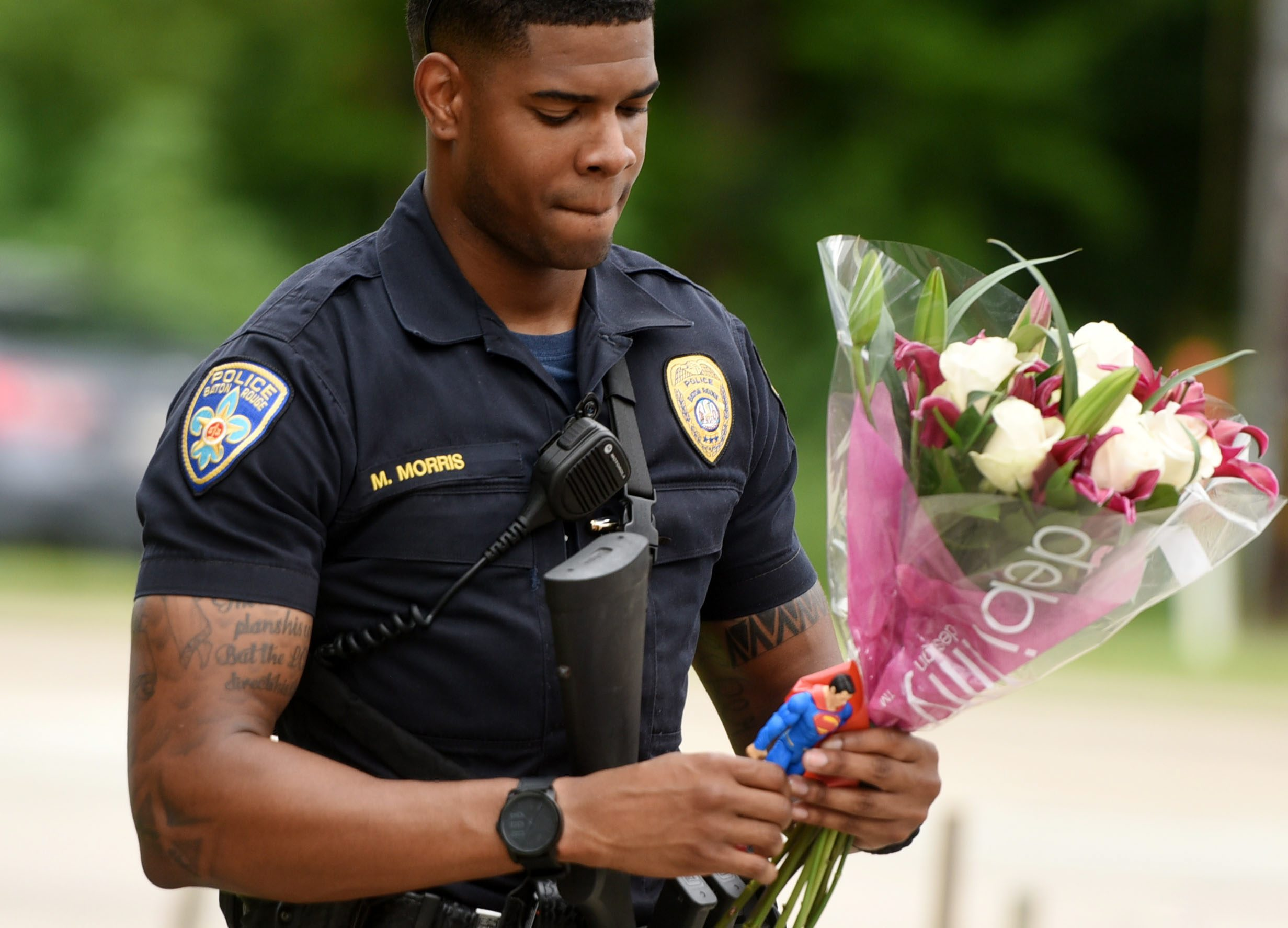 Baton Rouge Police Department Officer Markell Morris holds a bouquet of flowers and a Superman action figure that a citizen left at the Our Lady of the Lake Hospital where the police officers were brought on July 17, 2016. Henrietta Wildsmith/The Times via AP.