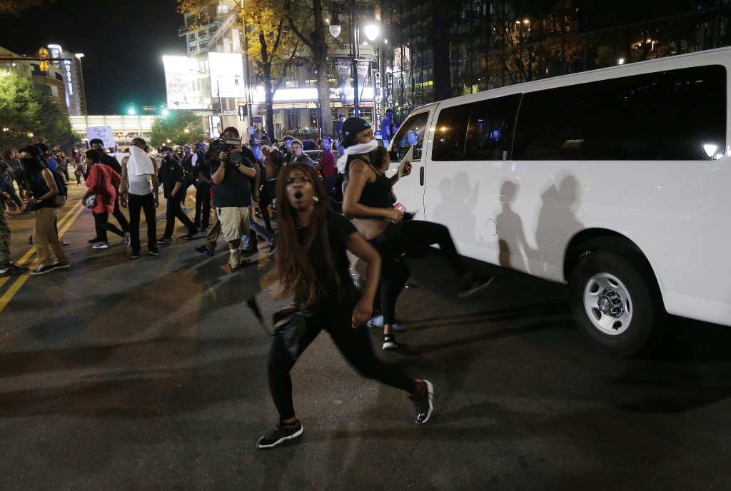 Demonstrators protest Tuesday's fatal police shooting of Keith Lamont Scott in Charlotte, N.C. on Wednesday, Sept. 21, 2016. Protesters rushed police in riot gear at a downtown Charlotte hotel and officers have fired tear gas to disperse the crowd. At least one person was injured in the confrontation, though it wasn't immediately clear how. Firefighters rushed in to pull the man to a waiting ambulance. (AP Photo/Chuck Burton)