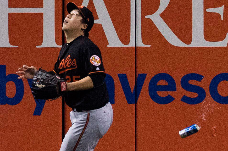 Baltimore Orioles' Hyun Soo Kim gets under a fly ball as a beer can sails past him during seventh inning American League wild-card game action against the Toronto Blue Jays in Toronto on Oct. 4, 2016. THE CANADIAN PRESS/Mark Blinch