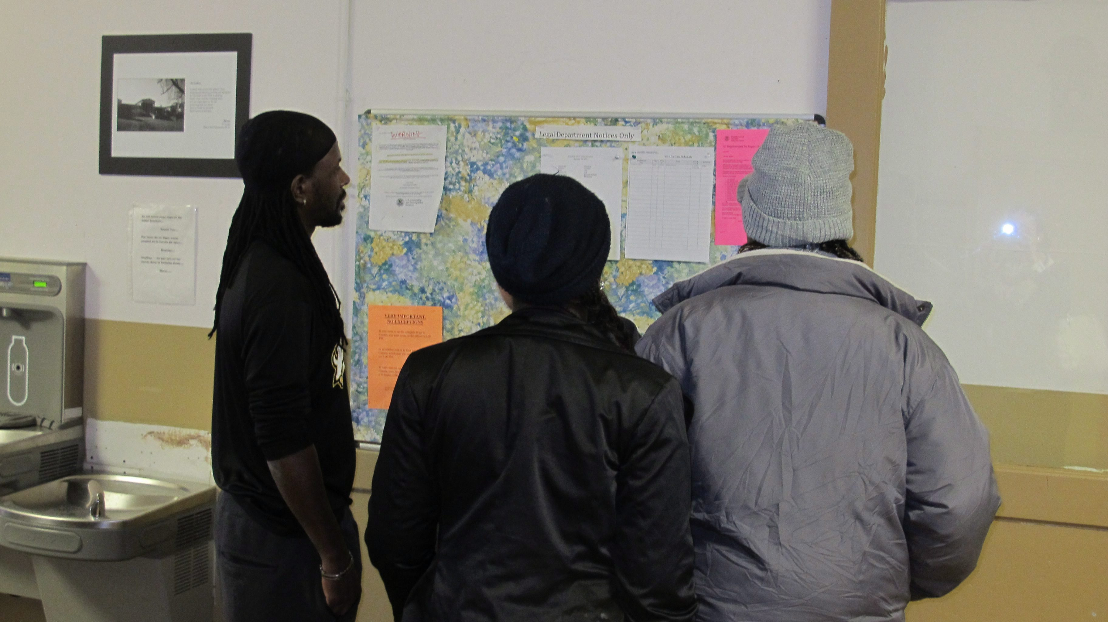 Asylum-seekers staying at the Vive La Casa shelter in Buffalo, N.Y., check to see whether they have been scheduled for an interview with Canadian immigration officials the following day. (AP Photo/Carolyn Thompson)