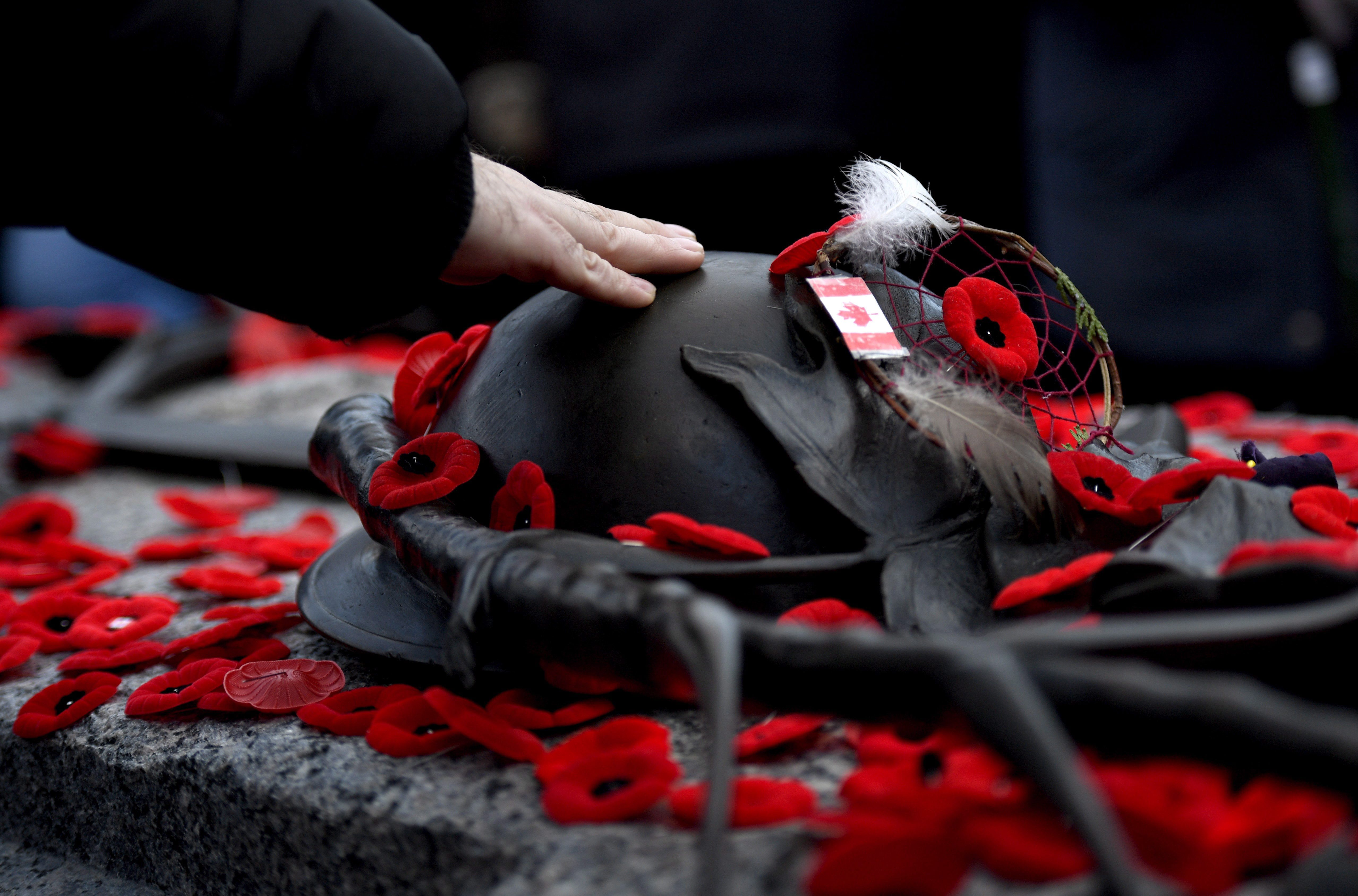 A man touches the helmet on the Tomb of the Unknown Soldier after laying a poppy following the National Remembrance Day Ceremony at the National War Memorial in Ottawa on Nov. 11, 2017. THE CANADIAN PRESS/Justin Tang