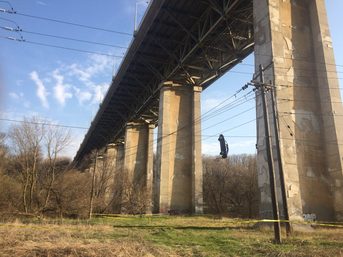 Mystery surrounds auto  hanging from bridge by a wire