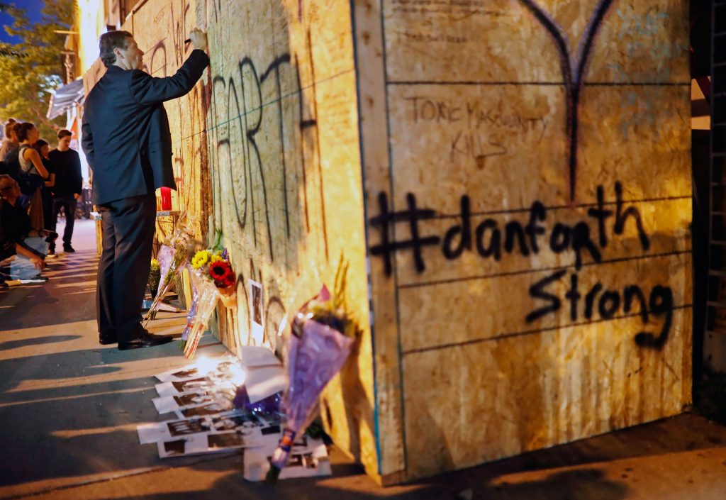 Toronto Mayor John Tory leaves a personal message on a makeshift memorial remembering the victims of a shooting on Sunday evening on Danforth Avenue on July 23, 2018. THE CANADIAN PRESS/Mark Blinch