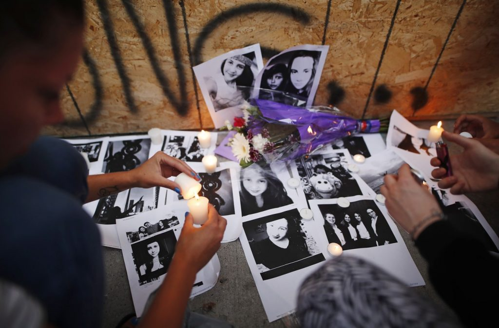 People light candles and leave photos of 18-year-old victim Reese Fallon at a memorial remembering the victims of a shooting on Danforth Avenue in Toronto on July 23, 2018. THE CANADIAN PRESS/Mark Blinch