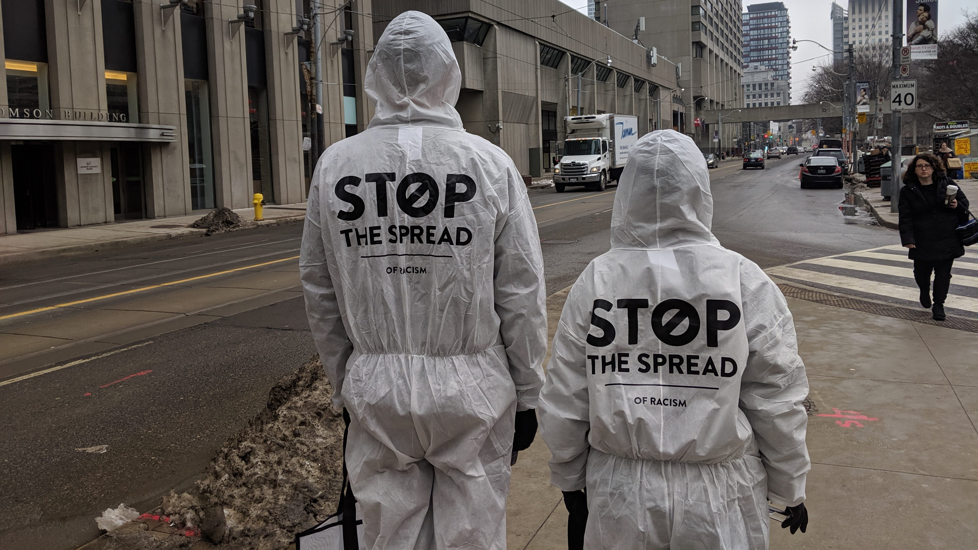 Volunteers with the Chinese Canadian National Council for Social Justice dressed in hazmat suits and handed out bottles of hand sanitizer outside City Hall on March 3
