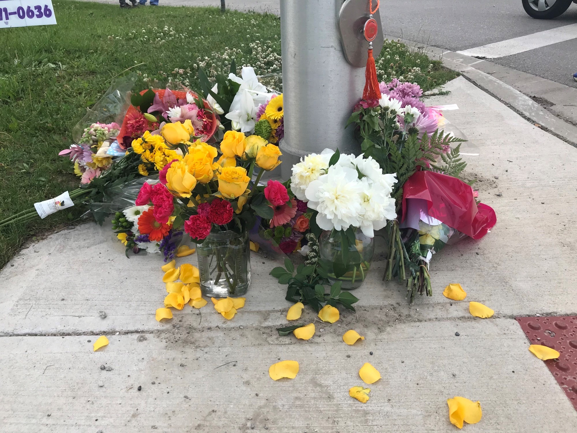 A small, makeshift memorial of flowers is pictured on June 7, 2021, on the London, Ontario sidewalk where a Muslim family of five was rundown by a vehicle in an attack police say was hate-motivated.